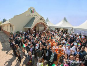 Crowd in front of worship building waving mini INC/South African flags