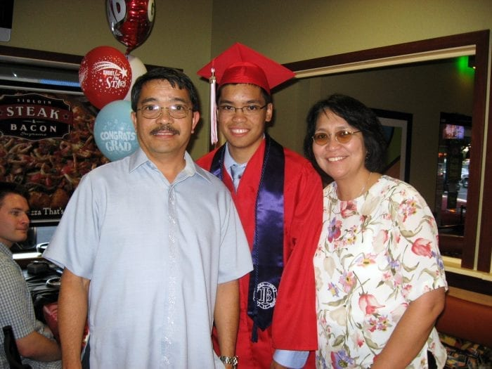 male student in cap and gown with parents