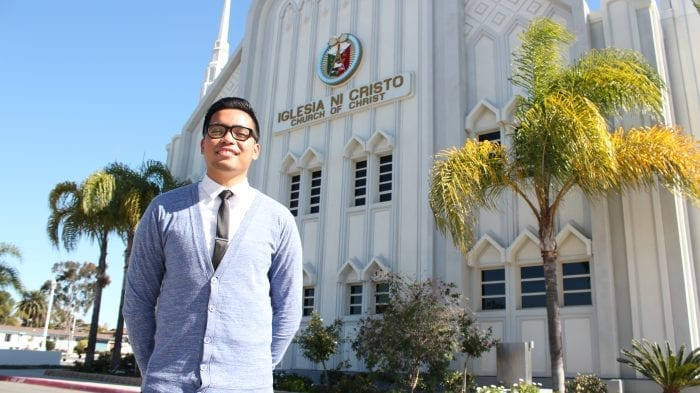 man smiling and standing in front of worship building