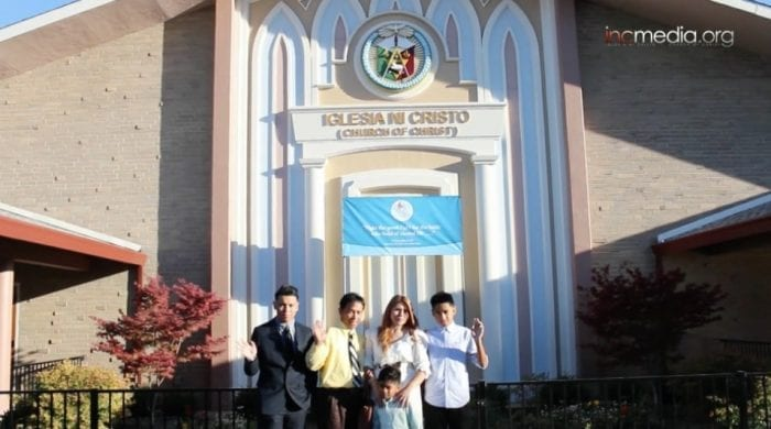 family posing for photo in front of worship building