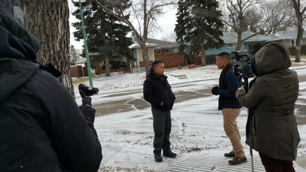 Nan Zapanta interviewing Mike Bigayan outside in the snow with 2 camera men recording them.