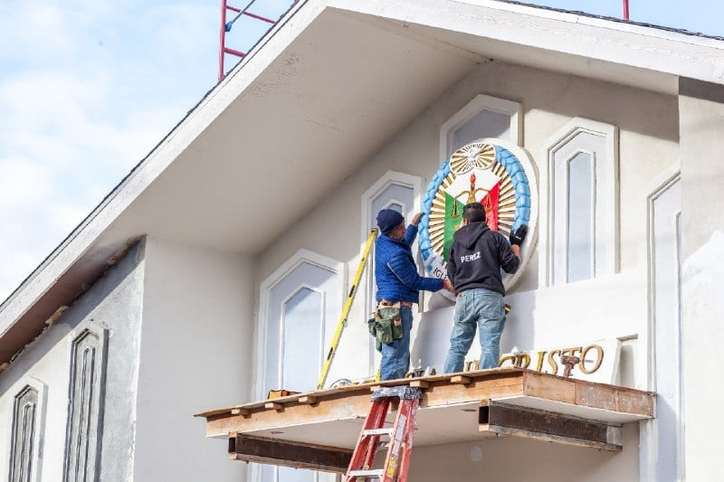 2 construction workers placing the seal of the Church of Christ onto the front facade of the house of worship.