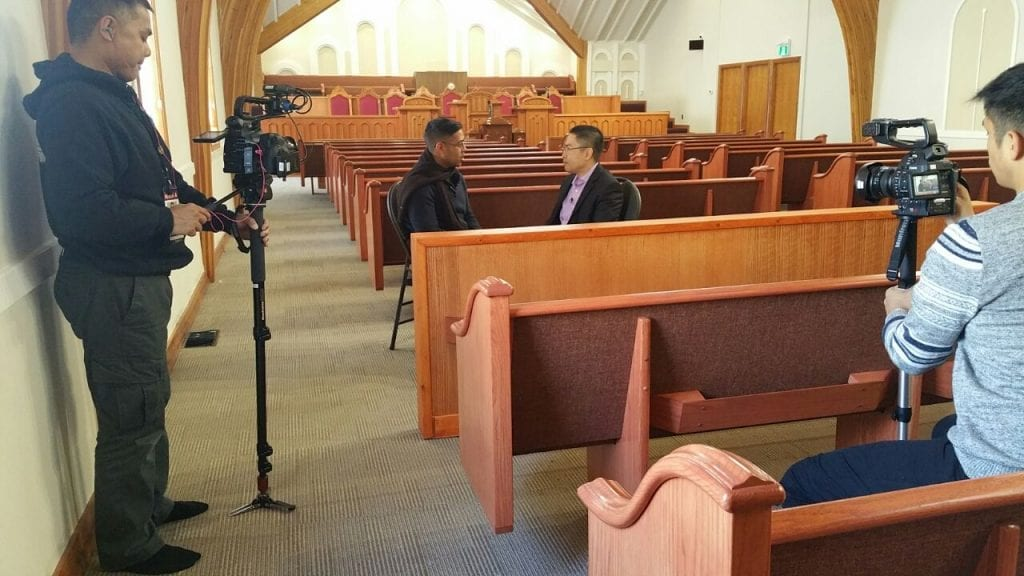 Behind the scenes of camera crew with Nan Zapanta interviewing Edwin Malang inside the sanctuary of the house of worship.