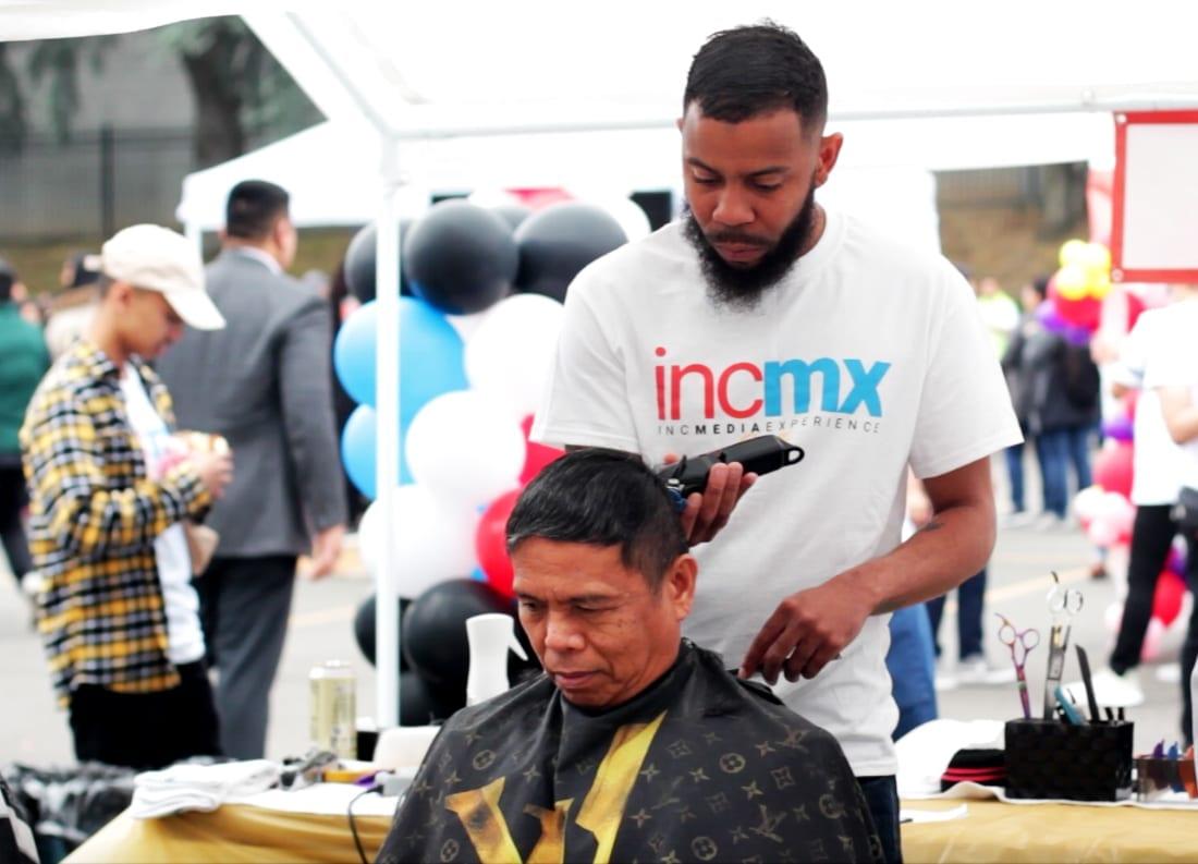 man giving someone a haircut at INCMX activity