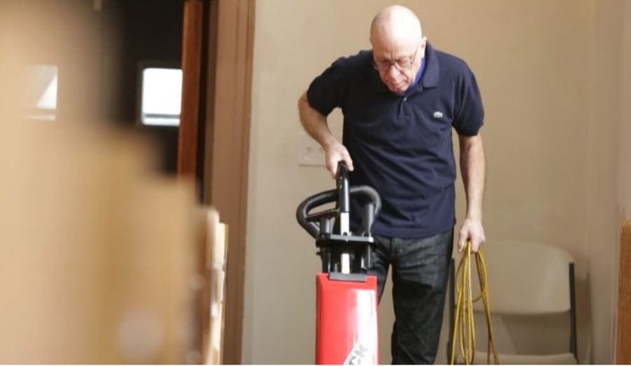Man vacuuming inside a the worship building