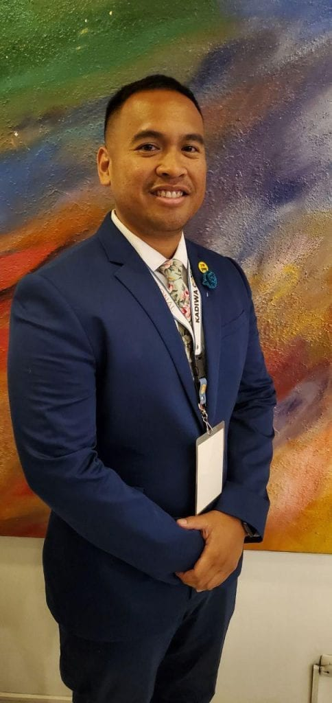 Michael Kani Rivera in a blue suit in front of a painting