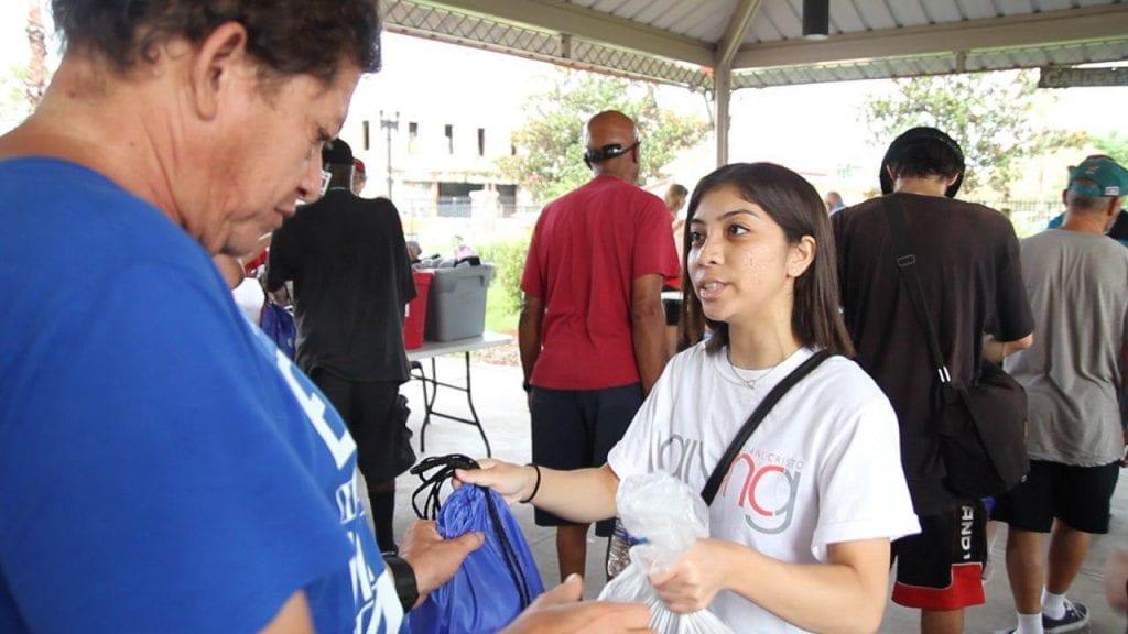 INC Giving Volunteer handing goods to community member in need.