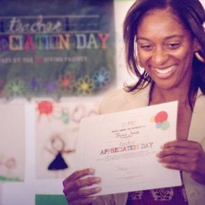 Teacher holding a Teacher Appreciation Day certificate.