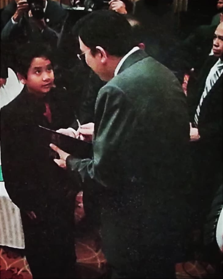 A boy getting an autograph from the Executive Minister.