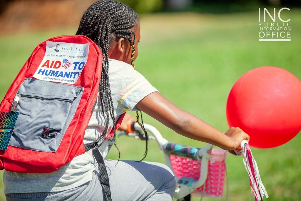 A little girl in Oakland rides away with a brand new backpack, courtesty of the FYM Foundation.