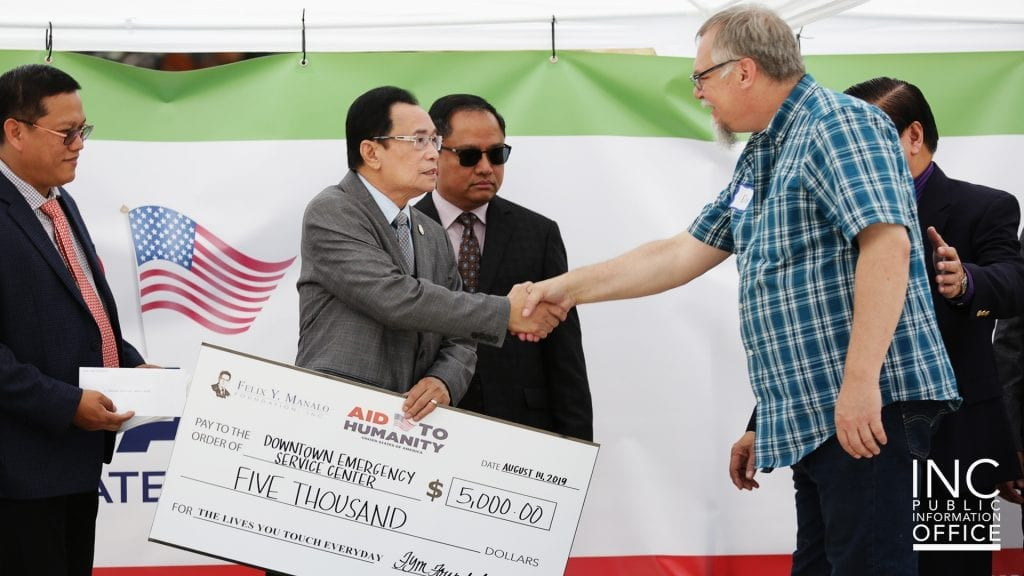 Two men shaking hands and exchanging a large donation check