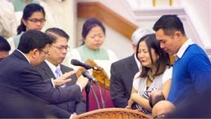 Executive Minister prays for a newborn while parents are carrying her up in the podium of the Bakersfield house of worship.