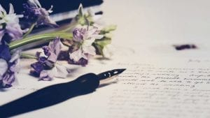 Handwritten note with calligraphy pen and a bunch of purple flowers.
