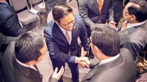 Looking down from above as a young man meets the Executive Minister and shakes his hand.