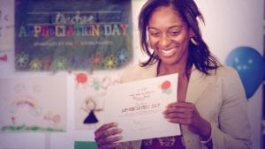 Woman holding a Teacher Appreciation Day Certificate smiling.