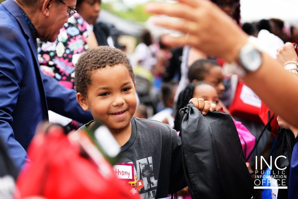 Smiling young boy accepting backpack of school supplies