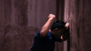 Man hitting a wall with his fist in anger